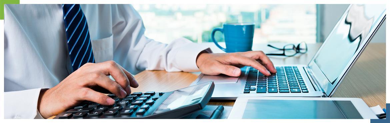 osoba używająca kalkulatora i laptopa